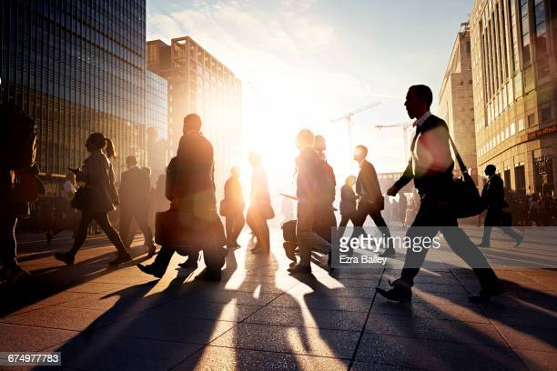 employees walking to work in the city at sunrise - finanzwirtschaft und industrie stock-fotos und bilder