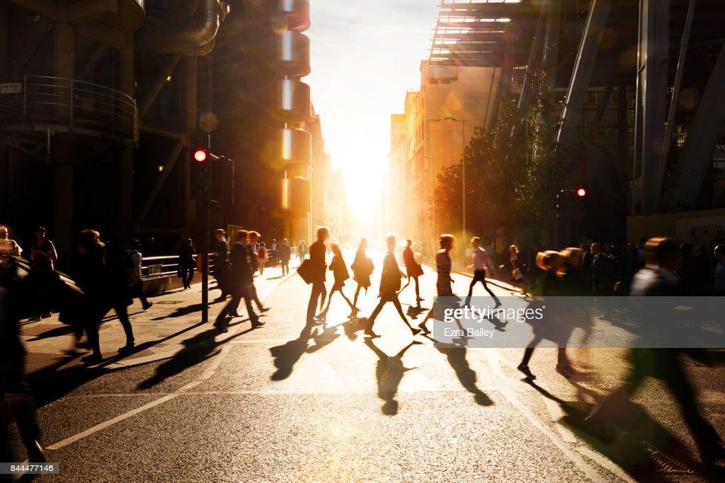 Business people walking through at city at dawn. : Stock Photo