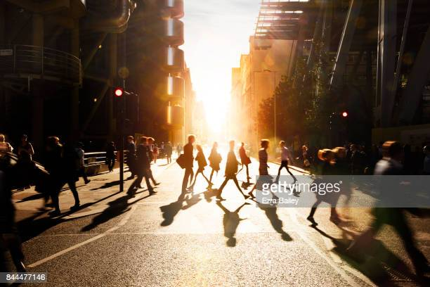 business people walking through at city at dawn. - routine stock-fotos und bilder