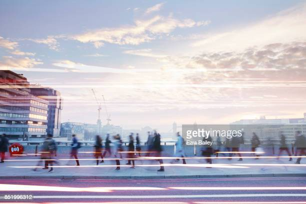 business people walking through the city at dawn. - in movimento foto e immagini stock