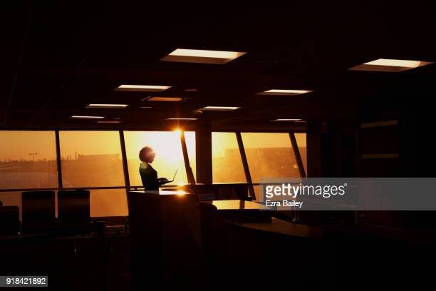 Young woman working on a laptop in an airport at sunset.