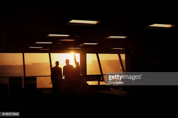 Business people watch the sunrise in an airport.