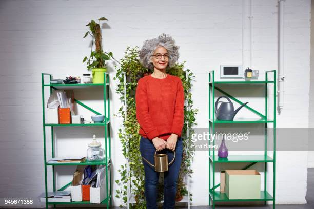 Portrait of woman watering plants in creative office space.