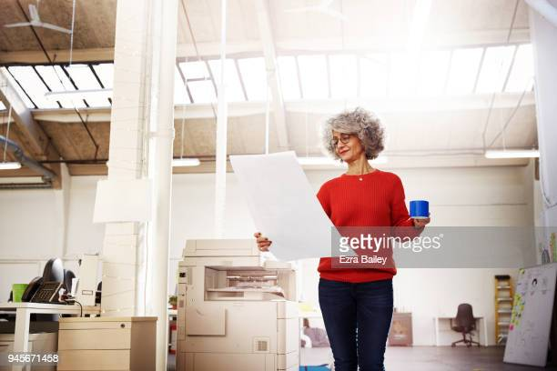 Woman in an industrial office looking at work and thinking of ideas.