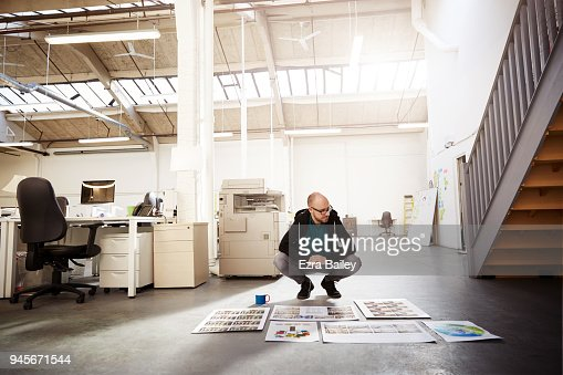 Creative man in an industrial office looking at work and thinking of ideas.