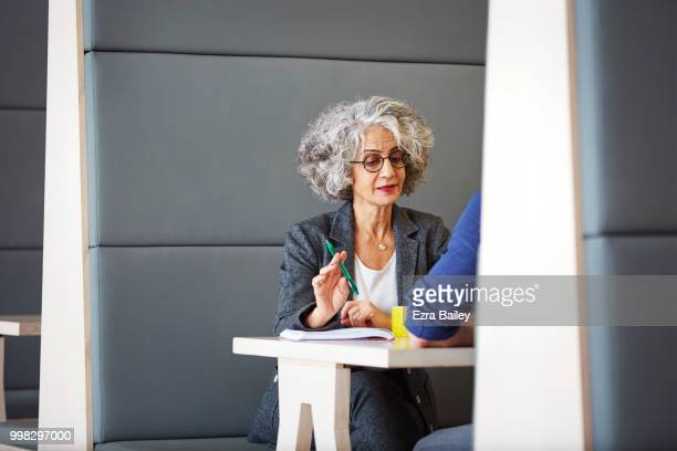 Professional woman discussing work in a clean modern open plan office.