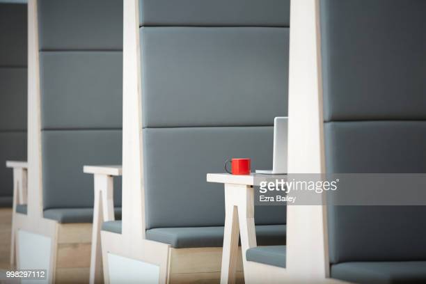 Laptop with red mug on a table in modern clean office.