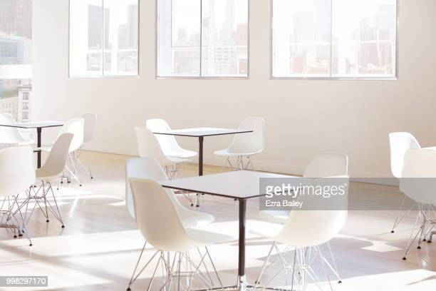 Empty tables and chairs in a clean modern office.