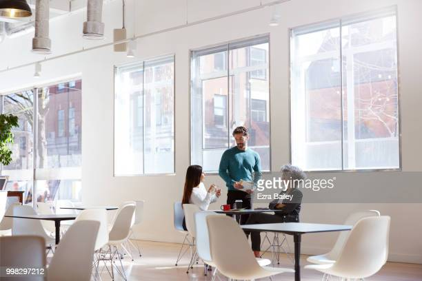 Employees catching up and discussing work in an open plan office.