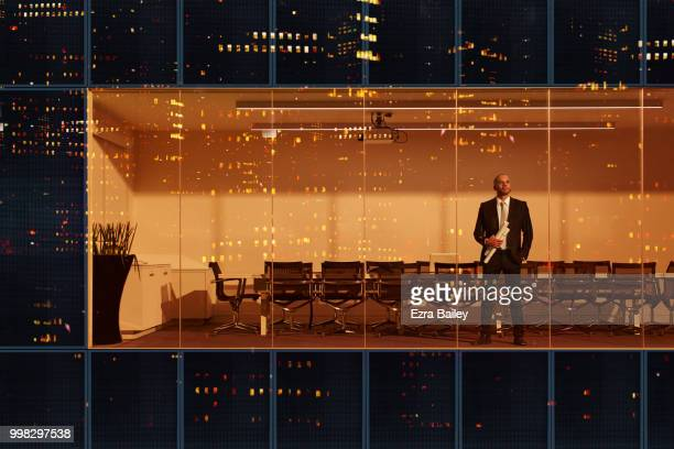 Portrait of a businessman looking out of a modern high rise office window at night.