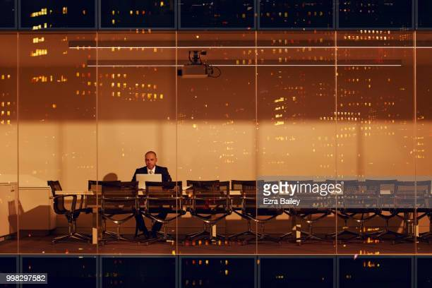 Businessman working late in a modern high rise office block at night.