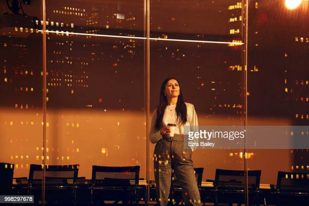 Portrait of a business woman looking out of a modern high rise office window at night.