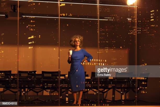 Business woman looking at the view over the city at night from an office boardroom.