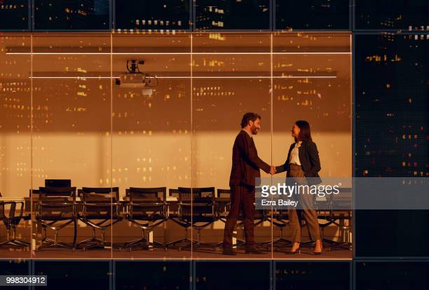 Business people closing a deal in the board room in a high rise office at night.