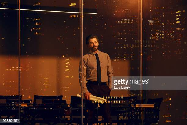 Businessman looking at the view over the city at night from an office boardroom.