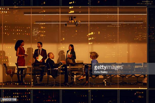 Business people working in a boardroom late at night overlooking the city.