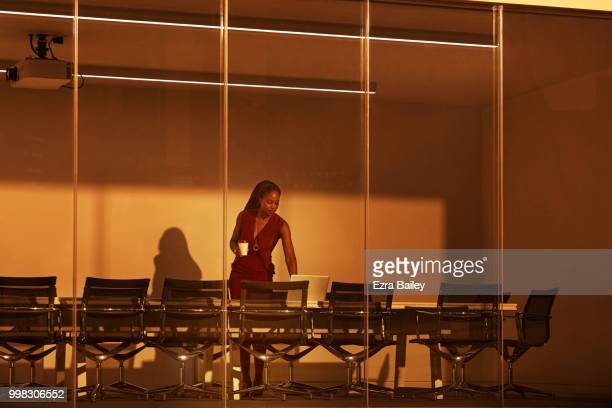 Business woman working in a boardroom at night over looking the city.