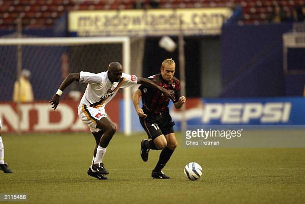 Ezra Hendrickson of the Los Angeles Galaxy runs for the ball against Joey DiGiamarino of the Metrostars during the game at Giants Stadium on June 21,...