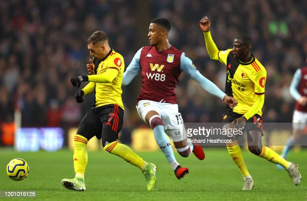 Ezri Konsa Ngoyo of Aston Villa battles for possession with Gerard Deulofeu and Abdoulaye Doucoure of Watford during the Premier League match between...