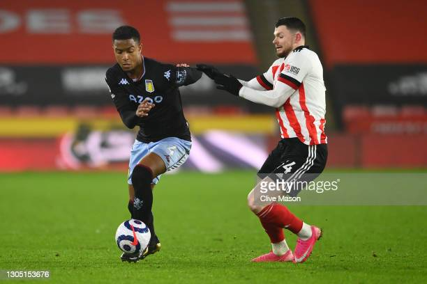 Ezri Konsa of Aston Villa and Oliver Burke of Sheffield United battle for the ball during the Premier League match between Sheffield United and Aston...