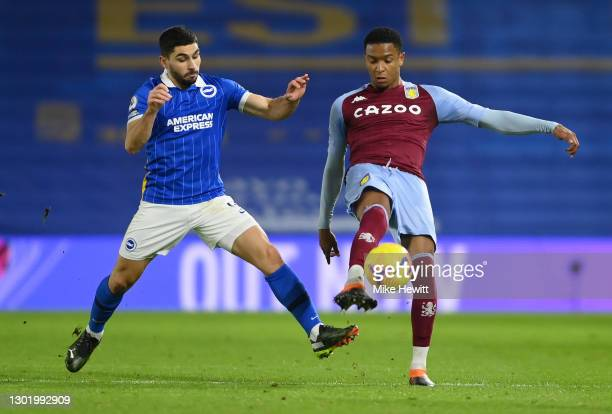 Ezri Konsa of Aston Villa is challenged by Neal Maupay of Brighton & Hove Albion during the Premier League match between Brighton & Hove Albion and...