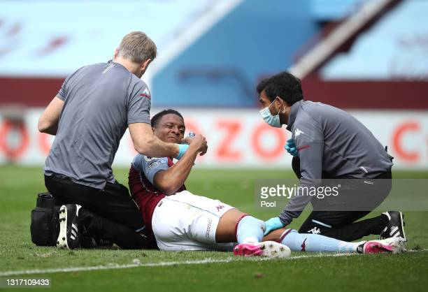 Ezri Konsa of Aston Villa receives medical treatment during the Premier League match between Aston Villa and Manchester United at Villa Park on May...