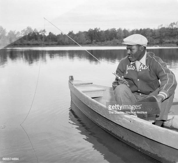 Ezzard Charles takes a break from training for his title fight with Rocky Marciano and goes fishing at Kutsher's Resort in Monticello New York May 20...