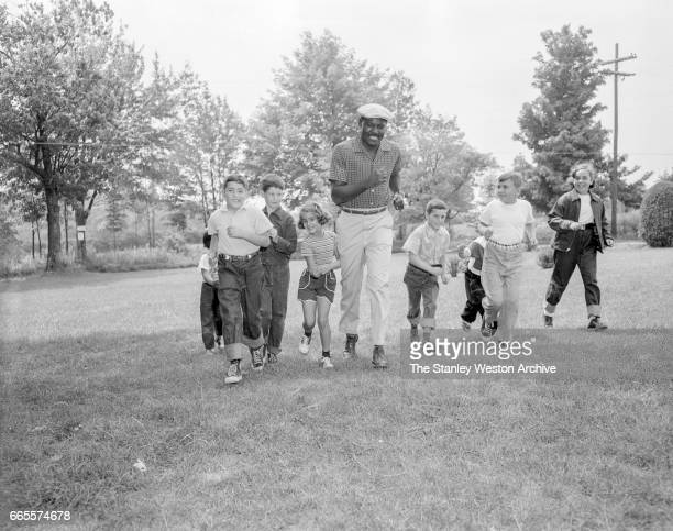 Ezzard Charles taking a jog with some young fans while he is preparing for his title fight with Rocky Marciano at Kutsher's Resort in Monticello New...