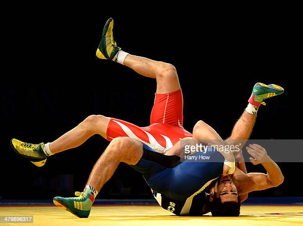 Ezzatolah Akbari Zarinkolaei of Iran is pinned by Akhmed Gadzhimagomedov of Russia during the 2014 FILA Freestyle Wrestling World Cup at The Forum on...