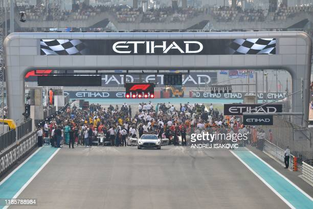 f1 cars and mechanics are pictured on the grid at the Yas Marina Circuit in Abu Dhabi ahead of the final race of the Formula One Grand Prix season on...