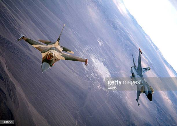 F16s from the 414th Red Flag Training Sq Nellis AFB Nevada fly in formation over the skies above the ranges north of Nellis after flying in a...