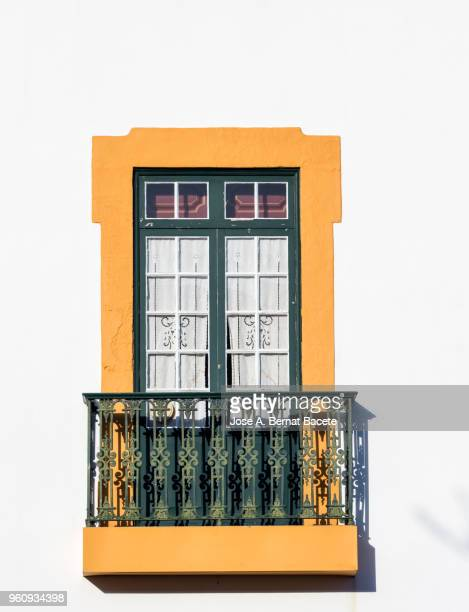 façade of an ancient house with a balcony of wood of colors in the city of angra do heroismo, a unesco world heritage site, on terceira island in the azores, portugal. - fachada arquitectónica fotografías e imágenes de stock