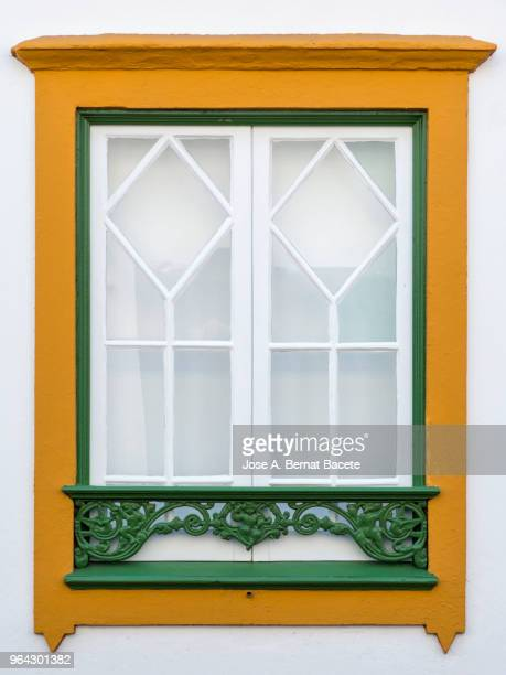façade of an ancient house with a window of wood of colors in the city of angra do heroismo, a unesco world heritage site, on terceira island in the azores, portugal. - cultura portuguesa fotografías e imágenes de stock