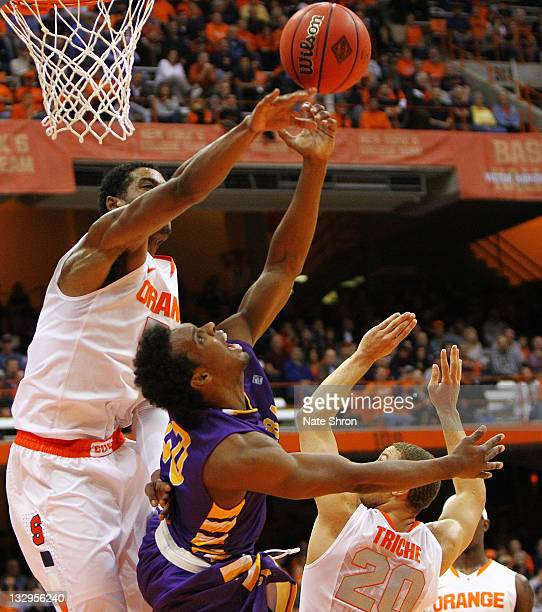 Fab Melo and Brandon Triche of the Syracuse Orange reach for the rebound against Gerardo Suero of the Albany Great Danes during the NIT Season Tipoff...