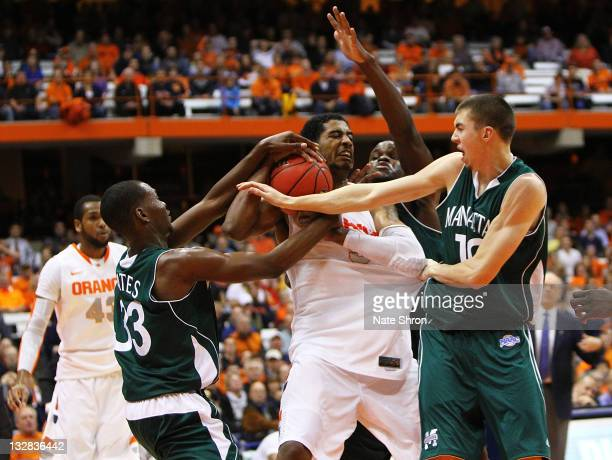 Fab Melo of the Syracuse Orange fights for the rebound against Donovan Kates Ryan McCoy and George Beamon of the Manhattan College Jaspers during the...