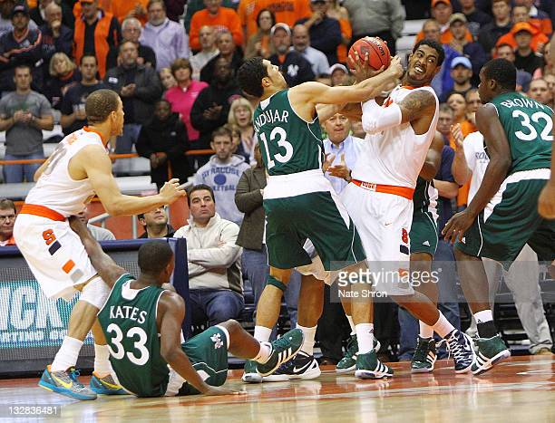 Fab Melo of the Syracuse Orange fights to maintain possession against Emmy Andujar of the Manhattan College Jaspers during the NIT Season Tipoff game...