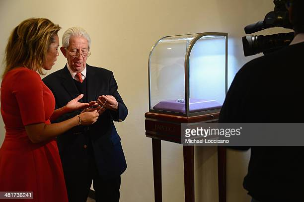 Faberge Curatorial Director Dr Geza von Habsburg shows off one of the Faberge egg pendant prizes to reporter Kemberly Richardson during the 2014...