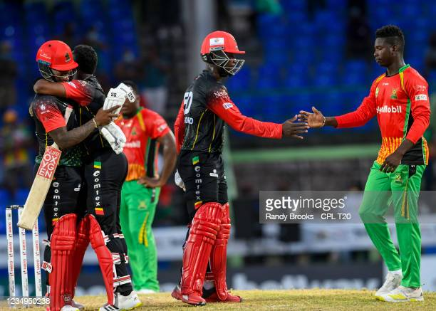 Fabian Allen and Dwayne Bravo hug as Sherfane Rutherford of Saint Kitts & Nevis Patriots is being congratulated by Kevin Sinclair of Guyana Amazon...