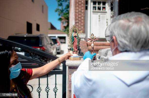 Fabian Arias, a Lutheran pastor with Saint Peter's Church in Manhattan, prepares to hold a service on the street in Brooklyn, for a group of...