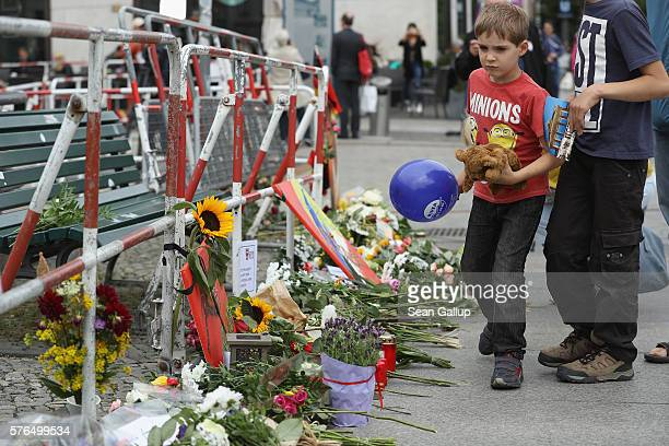 Fabian arrives with his brother and father to lay a teddy bear among flowers left by mourners outside the French Embassy the day after the terror...