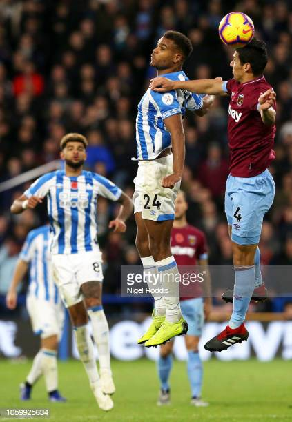 Fabian Balbuena of West Ham United battles for possession with Steve Mounie of Huddersfield Town during the Premier League match between Huddersfield...
