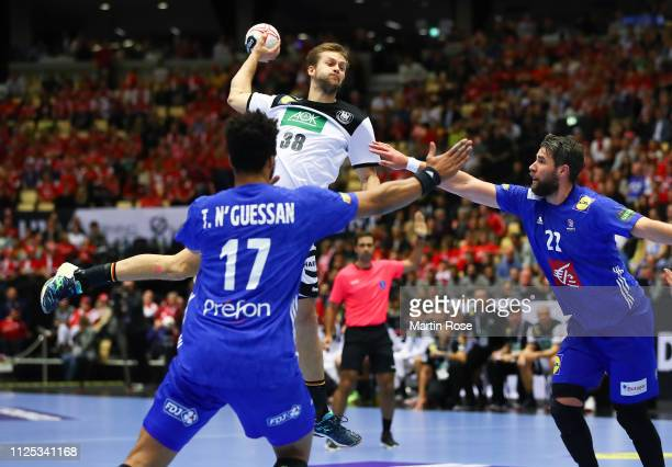 Fabian Bohm of Germany is challenged by Ludovic Fabregas of France during the 26th IHF Men's World Championship 3rd place match between Germany and...