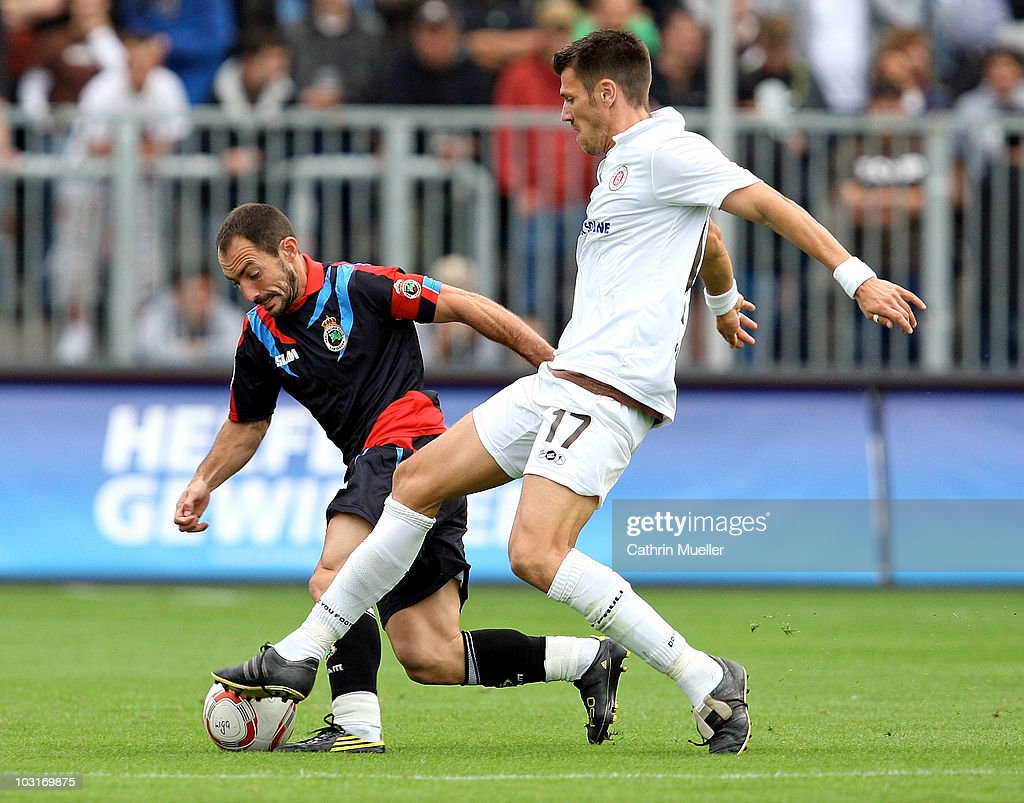 Fabian Boll of St. Pauli battles for the ball with P. Munitis of Santander during the pre-season friendly match between FC St. Pauli and Racing Santander at Millerntor Stadium on July 30, 2010 in Hamburg, Germany.