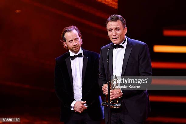 Fabian Busch and Oliver Masucci are seen on stage during the Bambi Awards 2016 show at Stage Theater on November 17, 2016 in Berlin, Germany.