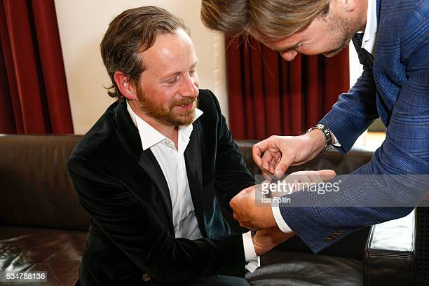 Fabian Busch hands over a Jaeger-LeCoultre watch for attending the Lola German Film Award 2016 at Sofitel on May 27, 2016 in Berlin, Germany.