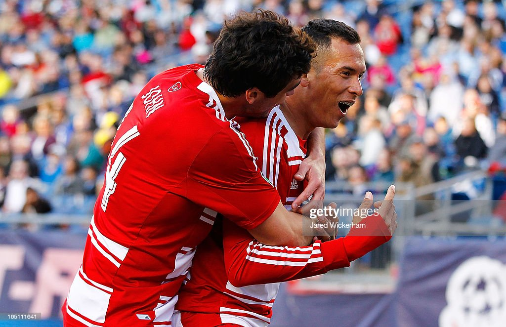 Fabian Castillo #7 of FC Dallas celebrates with teammate George John #14 of FC Dallas after scoring a goal late in the second half against the New England Revolution during the game at Gillette Stadium on March 30, 2013 in Foxboro, Massachusetts.