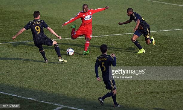 Fabian Castillo of FC Dallastakes a shot past defenders Sebastien Le Toux Raymon Gaddis and Vincent Nogueira of Philadelphia Union at PPL Park on...