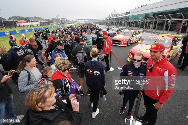 Fabian Coulthard driver of the Shell VPower Racing Team Ford Falcon FGX poses for a photo with a fan during the Supercars Phillip Island 500 at...