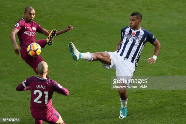 Fabian Delph and David Silva of Manchester City try and stop Salomon Rondon of West Bromwich Albion during the Premier League match between West...