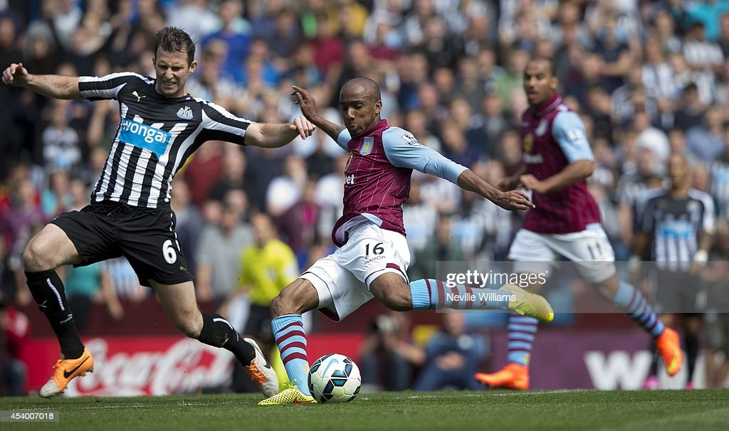 Fabian Delph (R) of Aston Villa is challenged by Mike Williamson of Newcastle United during the Barclays Premier League match between Aston Villa and Newcastle United at Villa Park on August 23, 2014 in Birmingham, England.
